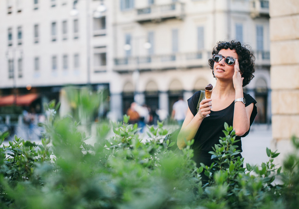 Photograph of woman in sunglasses eating icecream outdoors