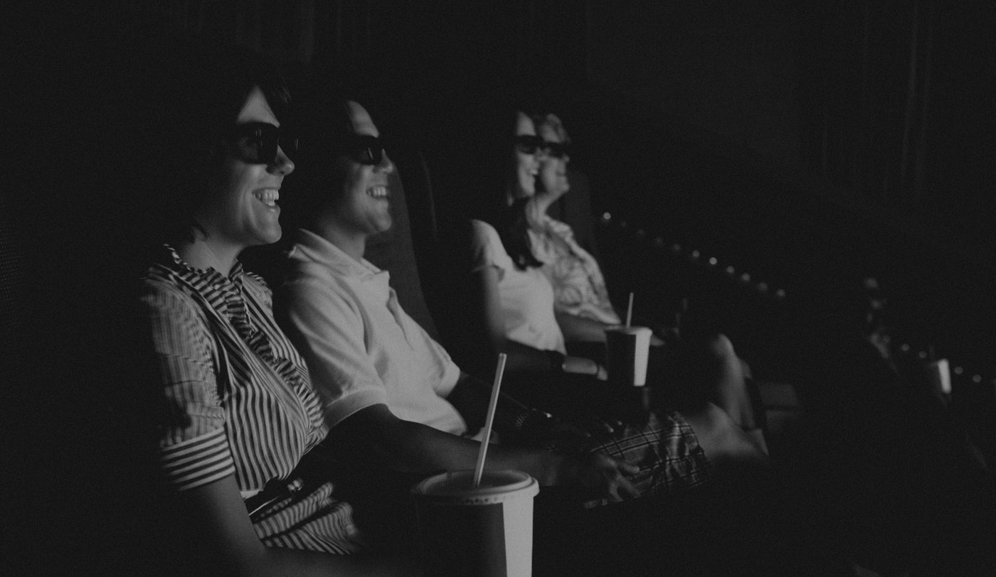 Photograph of people in a movie theatre with 3D glasses on