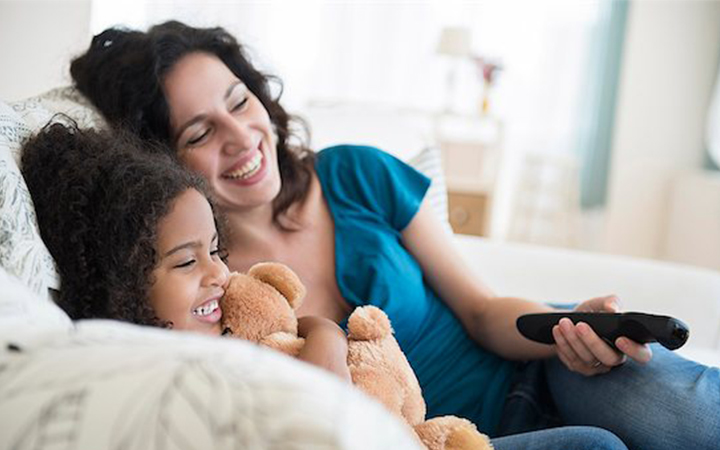 Mother and daughter watching a movie at home