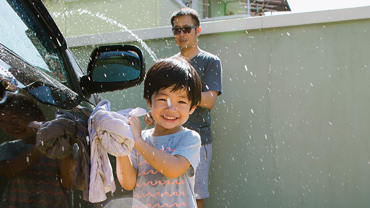 Father and young son washing a car