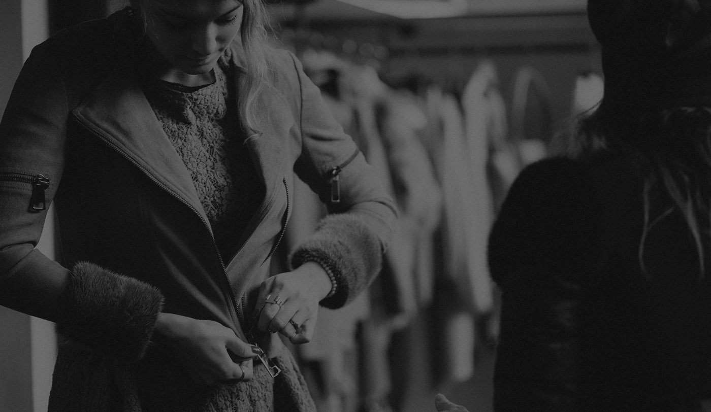 Photograph of a woman trying on a coat in a shop