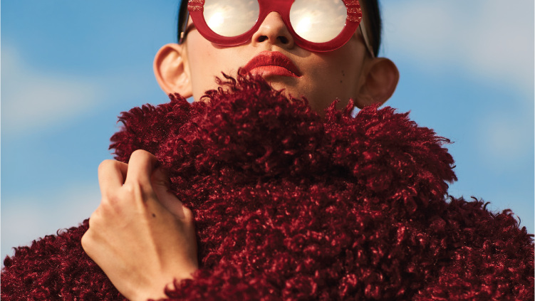 Woman in red coat and sunglasses stares at sky
