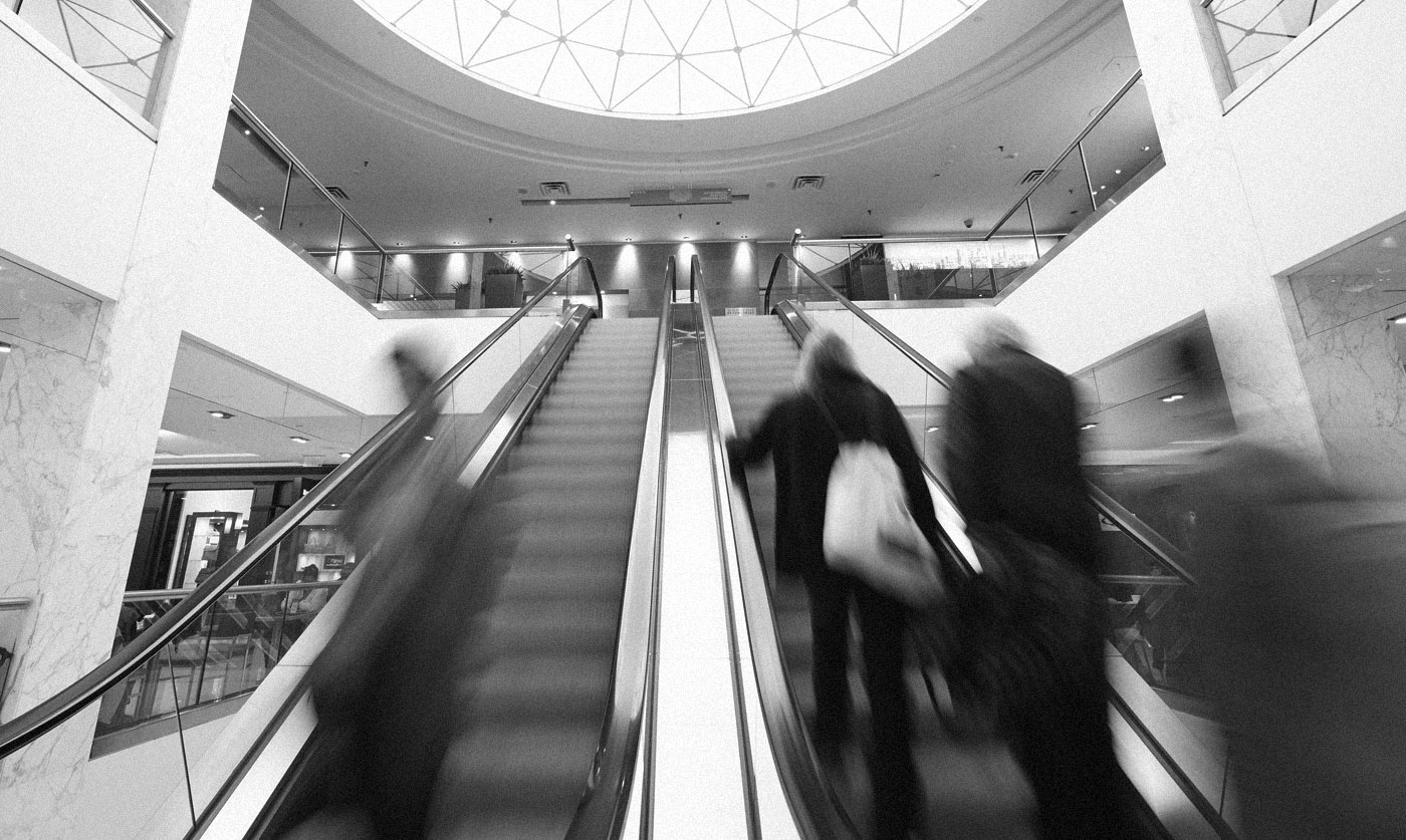 Photograph of people moving on an escalator