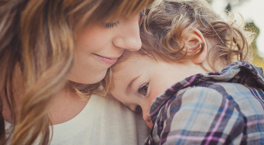 Image of boy snuggling with his mother