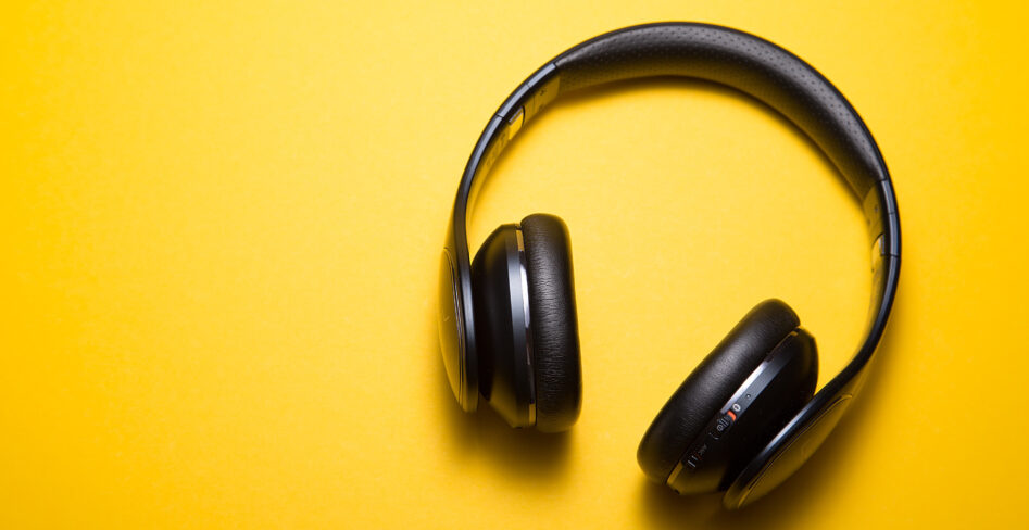 black headphones on a solid yellow background